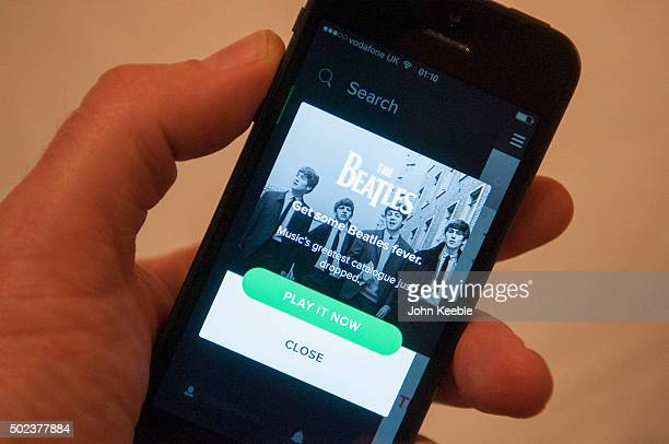 In this photo illustration A man holds a mobile phone displaying the Spotify app announcing the Beatles music collection is now available for...