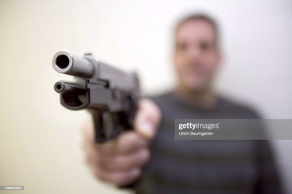 In this photo illustration a man holds a pistol in his hand on November 22, 2012 in Bonn, Germany.