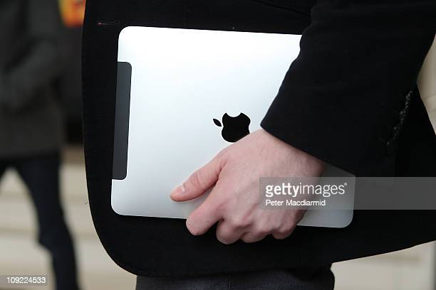 In this photo illustration a man holds an Apple ipad tablet on February 17 2011 in London England Apple sold two million ipads in the first two...