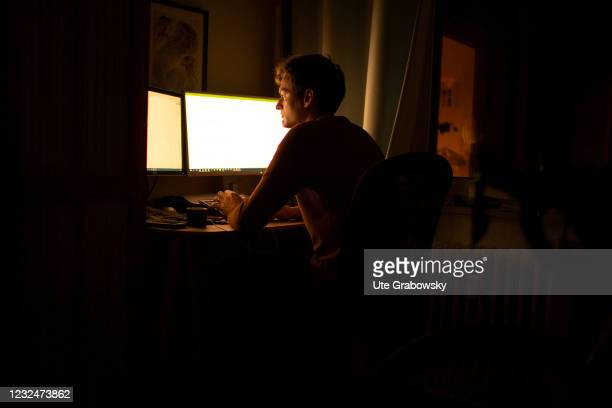 In this photo illustration a man is working on computer at night on April 20, 2021 in Bonn, Germany.