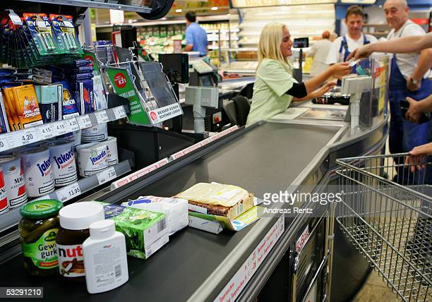 In this photo illustration a man pays for his groceries at the cash register in a supermarket on July 26 2005 in Luneburg Germany Sparked by the...