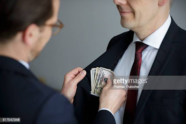 In this Photo Illustration a man put dollar bills in the pocket of a man on March 23 2016 in Berlin Germany