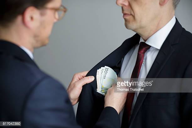 In this Photo Illustration a man put euro bills in the pocket of a man on March 23 2016 in Berlin Germany