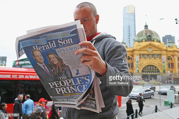In this photo illustration a man reads a copy of the local Melbourne newspaper 'The Herald Sun' showing the reaction to the birth of the Duke And...