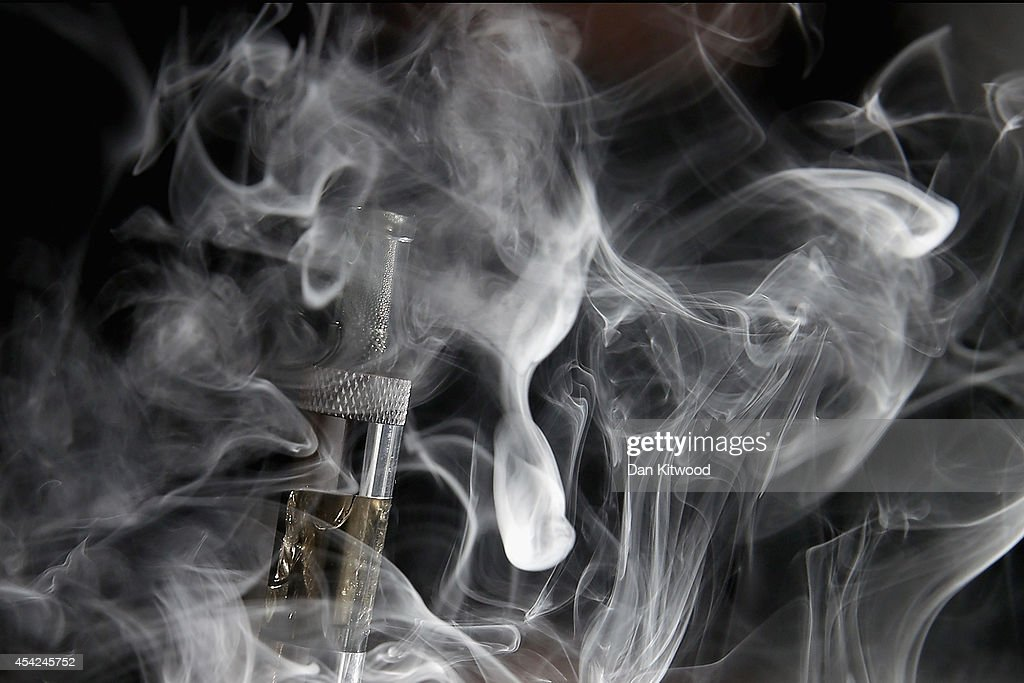 In this photo illustration, a man smokes an E-Cigarette at the V-Revolution E-Cigarett shop in Covent Garden on August 27, 2014 in London, England. The Department of Health have ruled out the outlawing of 'e-cigs' in enclosed spaces in England, despite calls by WHO, The World Health Organisation to do so. WHO have recommended a ban on indoor smoking of e-cigs as part of tougher regulation of products dangerous to children.