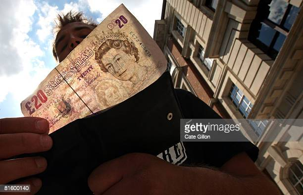In this photo illustration a man takes a 20 pound note from his wallet outside a bank on June 17 2008 in London England The governor of the Bank of...