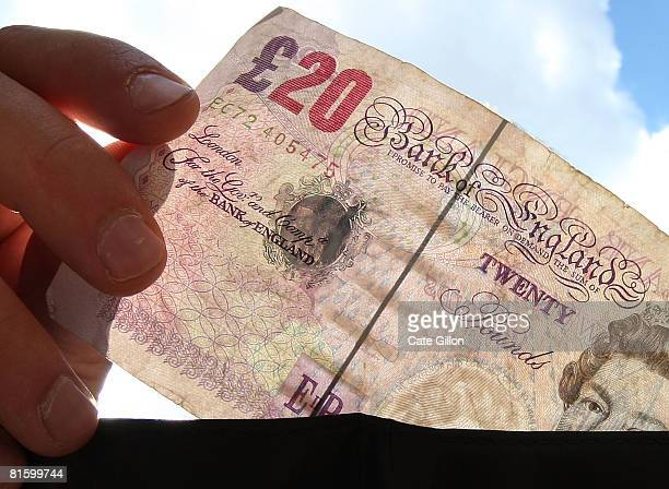 In this photo illustration a man takes a twenty pound note from his wallet on June 17 2008 in London England The governor of the Bank of England has...