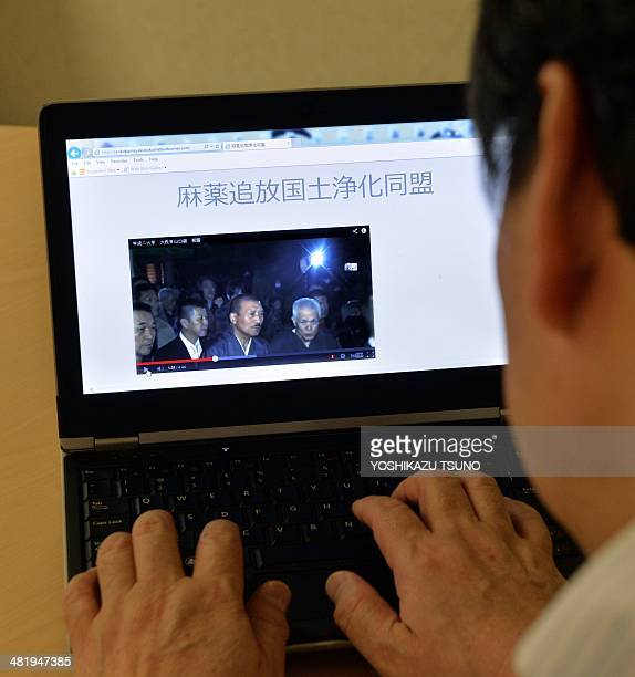 """In this photo illustration a man uses a laptop to browse a home page of the """"Banish Drugs and Purify the Nation League"""" website displaying a video..."""