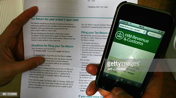 In this photo illustration a man views a tax return form on April 22 2009 in Glasgow Scotland Chancellor Alistair Darling has raised income tax in...