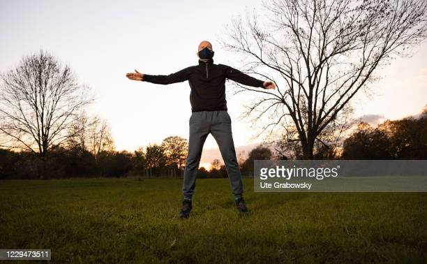 In this photo illustration a man, wearing a mask, is doing jumping jack in times of corona pandemie on November 04, 2020 in Bonn, Germany.