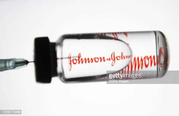In this photo illustration a medical syringe and a vial with fake coronavirus vaccine seen in front of the Johnson & Johnson logo.
