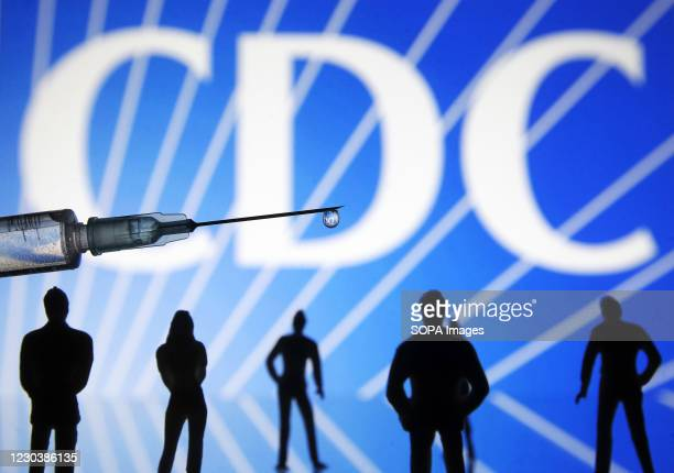 In this photo illustration a medical syringe and small figures of people are seen in front of the Centers for Disease Control and Prevention logo....