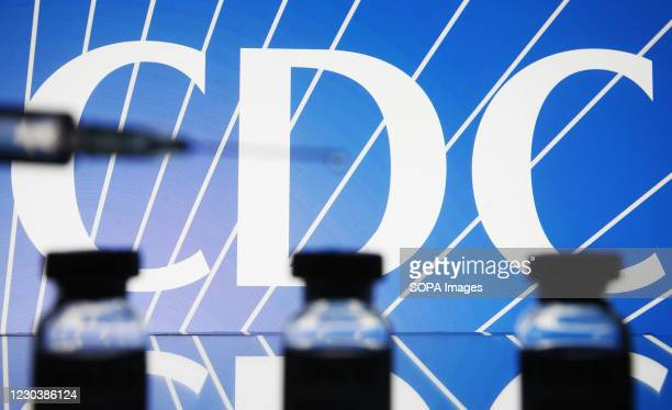 In this photo illustration a medical syringe and vials are seen in front of the Centers for Disease Control and Prevention logo. The World Health...
