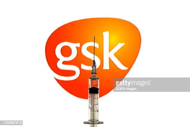In this photo illustration a medical syringe seen displayed in front of the GlaxoSmithKline logo.