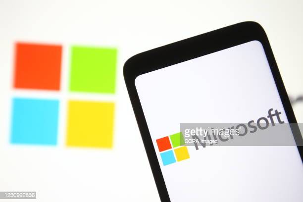 In this photo illustration a Microsoft logo is seen on a mobile phone and a pc screen.