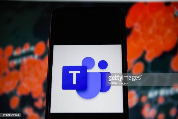 In this photo illustration a Microsoft teams logo is seen displayed on a smartphone with a World map of COVID 19 epidemic on the background
