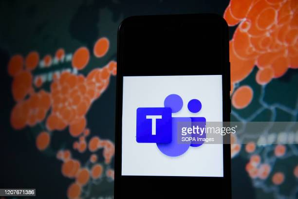 In this photo illustration a Microsoft Teams logo seen displayed on a smartphone with a World map of COVID 19 epidemic on the background