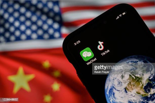 In this photo illustration, a mobile phone can be seen displaying the logos for Chinese apps WeChat and TikTok in front of a monitor showing the...