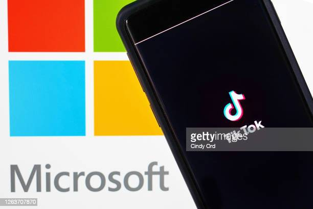 In this photo illustration, a mobile phone featuring the TikTok app is displayed next to the Microsoft logo on August 03, 2020 in New York City....