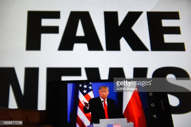 In this photo illustration a mobile phone shows President of United States of America Donald Trump with a sentence saying Fake News in the background