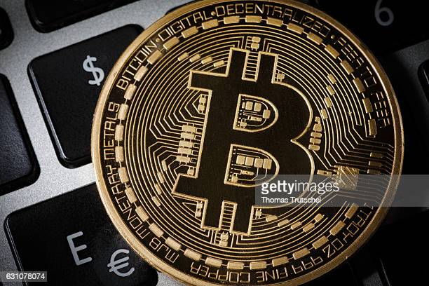 In this photo illustration a model Bitcoin is placed on a computer keyboard next to the symbols for euro and dollars on January 06 2017 in Berlin...