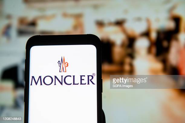 In this photo illustration a Moncler logo seen displayed on a smartphone