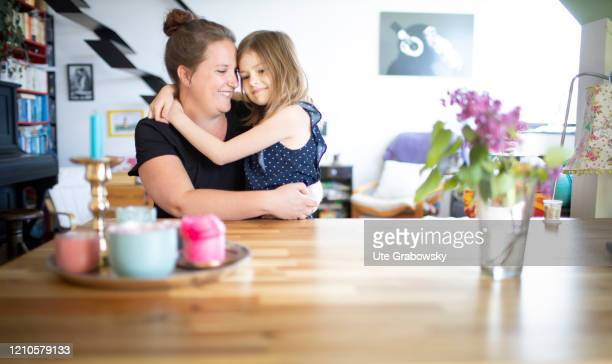 In this photo illustration a mother and a seven year old girl are sitting cheek to cheek on April 15 2020 in Bonn Germany