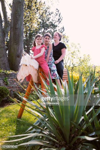 In this photo illustration a mother and her daughters are sitting on a wooden horse in the garden on April 15 2020 in Bonn Germany