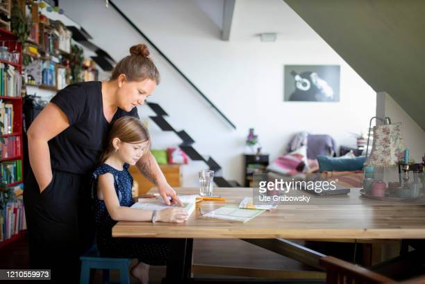 In this photo illustration a mother helps her daughter with her schoolwork. In times of Corona the children have to learn at home and keep social...