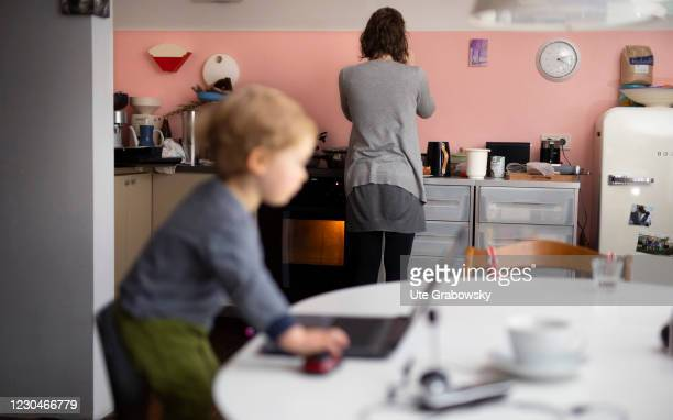 In this photo illustration a mother is doing homework while the child has climbed up a chair and is olaying with her laptop on January 07, 2021 in...