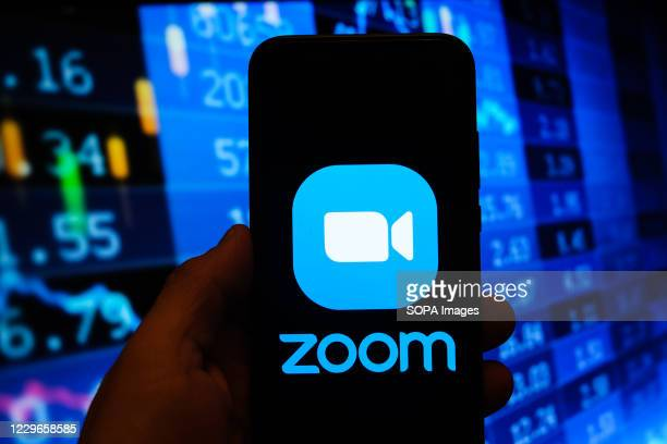In this photo illustration a multiple exposure image shows a Zoom video logo displayed on a smartphone with stock market percentages in the...