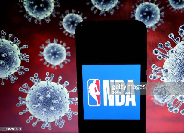 In this photo illustration a National Basketball Association logo seen displayed on a smartphone with a computer model of the COVID19 coronavirus in...