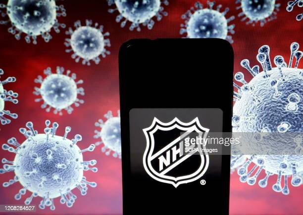 In this photo illustration a National Hockey League logo seen displayed on a smartphone with a computer model of the COVID-19 coronavirus the...