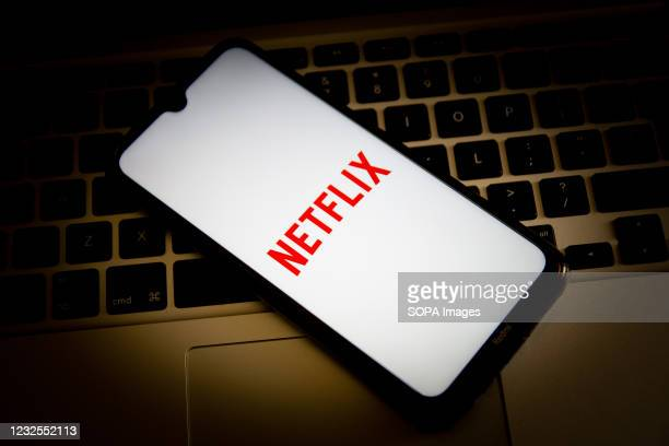 In this photo illustration, a Netflix logo seen displayed on a smartphone screen with a computer keyboard in the background.