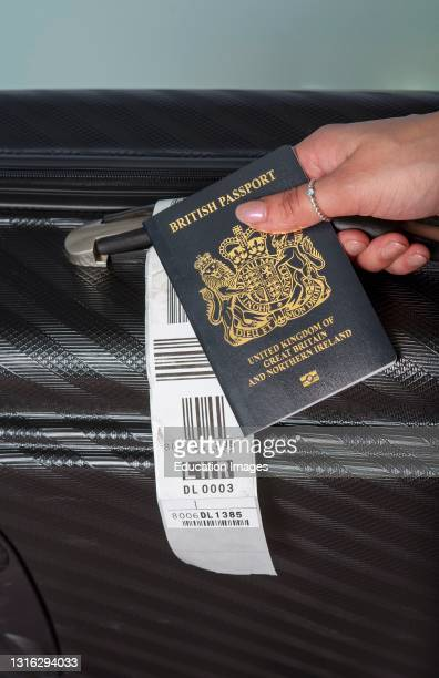 In this photo illustration, a new dark blue colored British passport held in a travellers hand with holiday suitcase.