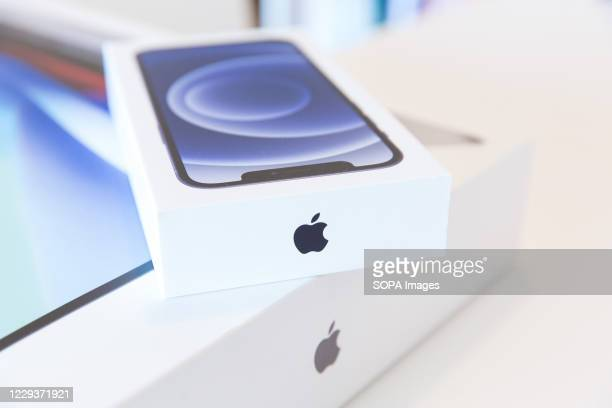 In this photo illustration a new iPhone 12 package on top of a MacBook Pro package.