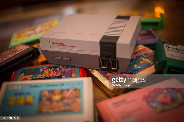 In this photo illustration, a Nintendo Classic Mini 'Nintendo Entertainment System' video game console first generation seen with a pile of Famicom...