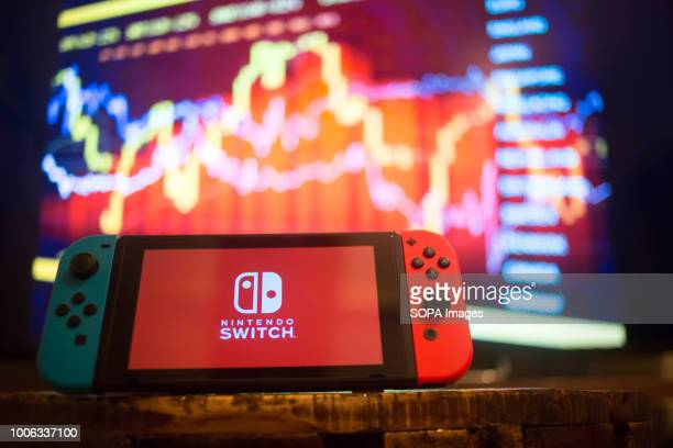In this photo illustration a Nintendo Switch displays the Nintendo Switch logo with a background of a market value on the stock exchange