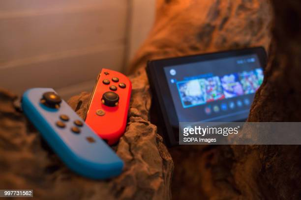 In this photo illustration a Nintendo Switch seen with two JoyCon detached from the screen