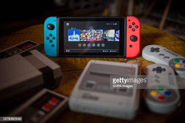 In this photo illustration a Nintendo Switch surrounded by a NES Classic Mini and a SNES Classic Mini video game consoles