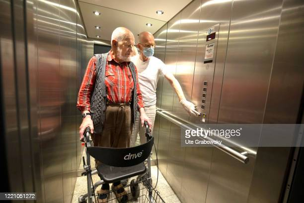 In this photo illustration a nurse helps a man in an elevator on June 11, 2020 in Bonn, Germany.
