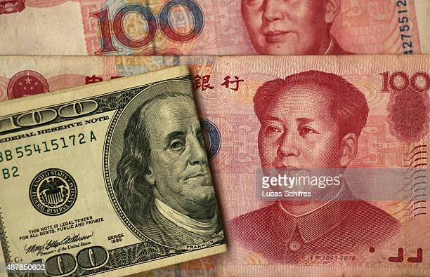 In this photo illustration a one hundred US dollar banknote featuring Benjamin Franklin is on display by two one hundred Chinese yuans banknotes...