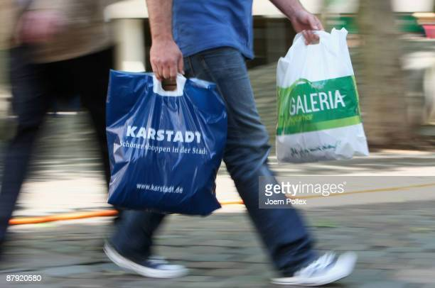 In this photo illustration a pedestrian walks along the street carrying plastic bags of the department stores Karstadt and Galeria Kaufhof on May 22...