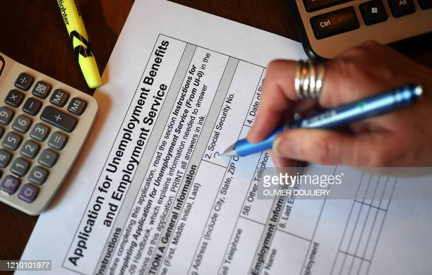 In this photo illustration a person files an application for unemployment benefits on April 16 in Arlington Virginia The government reported Thursday...