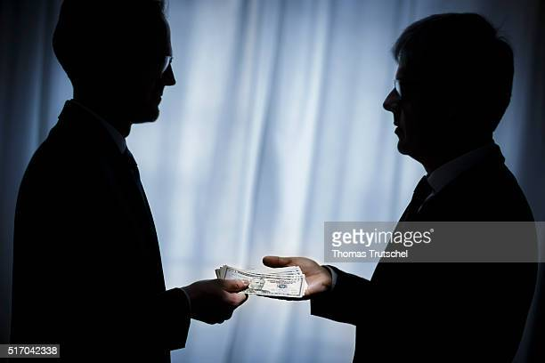 In this Photo Illustration a person hand over dollar bills to another person on March 23 2016 in Berlin Germany