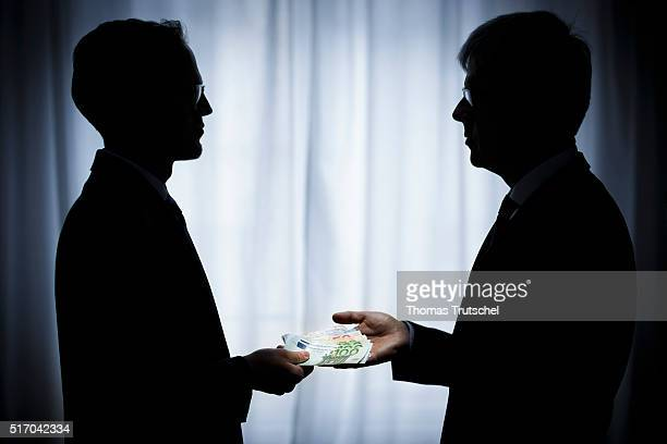 In this Photo Illustration a person hand over euro bills to another person on March 23 2016 in Berlin Germany