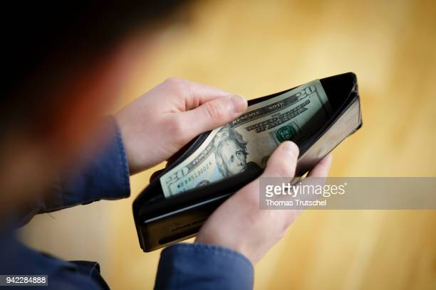 In this photo illustration a person hold a wallet filled with Dollar bills on April 05 2018 in Berlin Germany