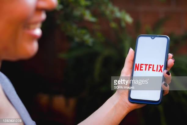 In this photo illustration a person holding a smartphone displaying the Netflix logo on a screen.