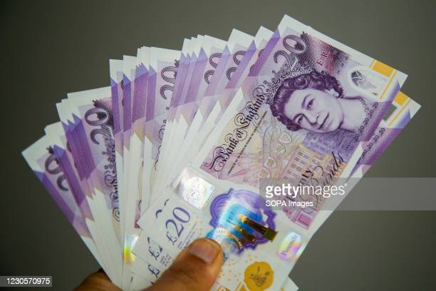 In this photo illustration, a person holding British twenty pound sterling banknotes.