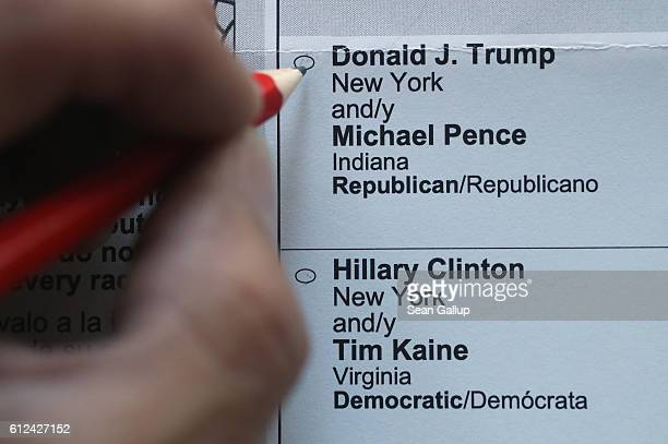 In this photo illustration a person holds a pencil over a genuine US expatriate's Maryland voting ballot for the 2016 US presidential elections on...